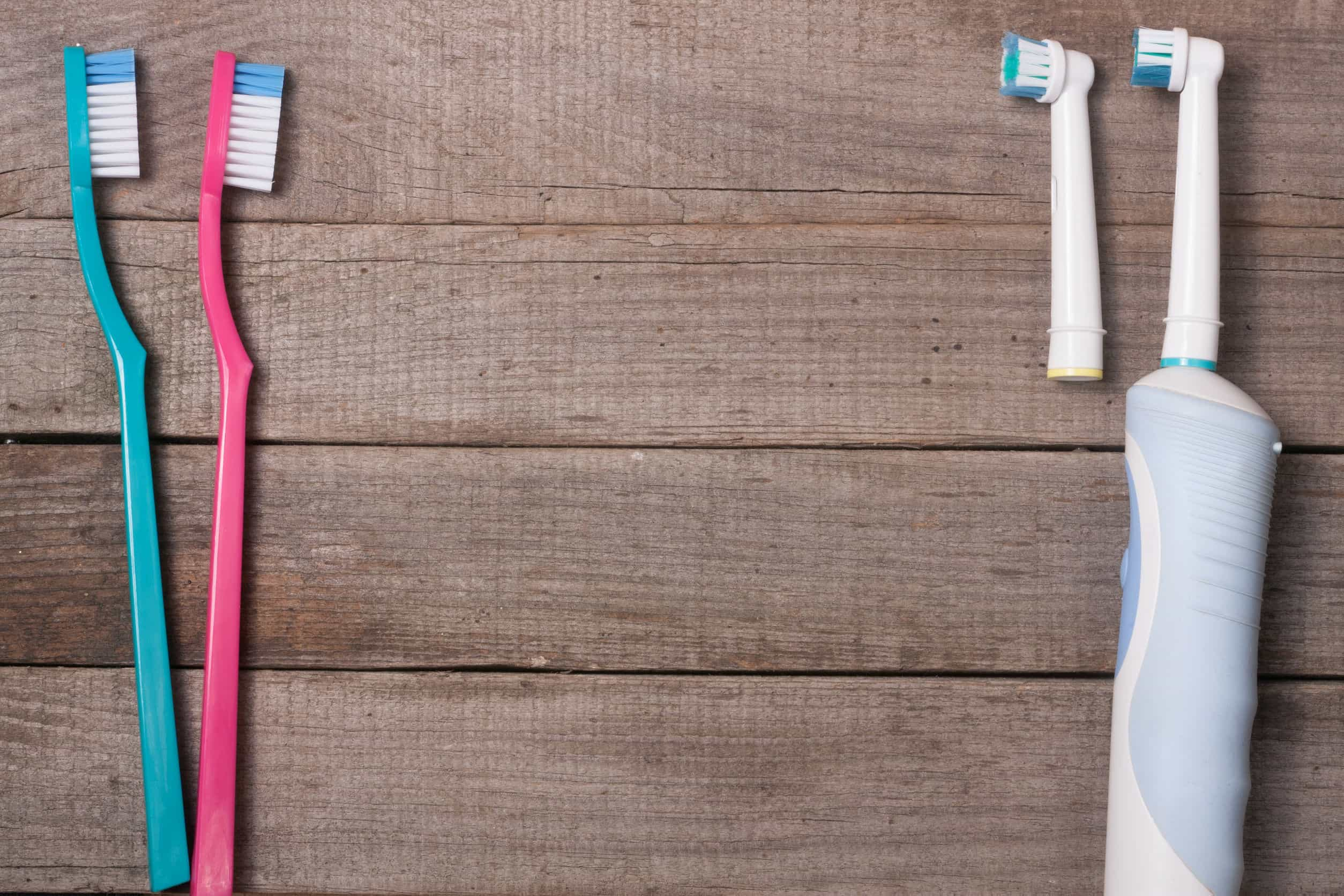 69471317 - electric and manual toothbrushes on the wooden background
