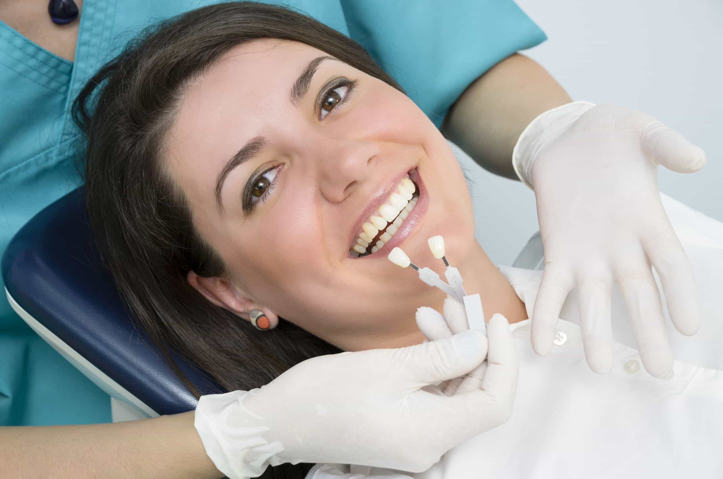 20442854 - a dentist showing porcelain teeth to pacient