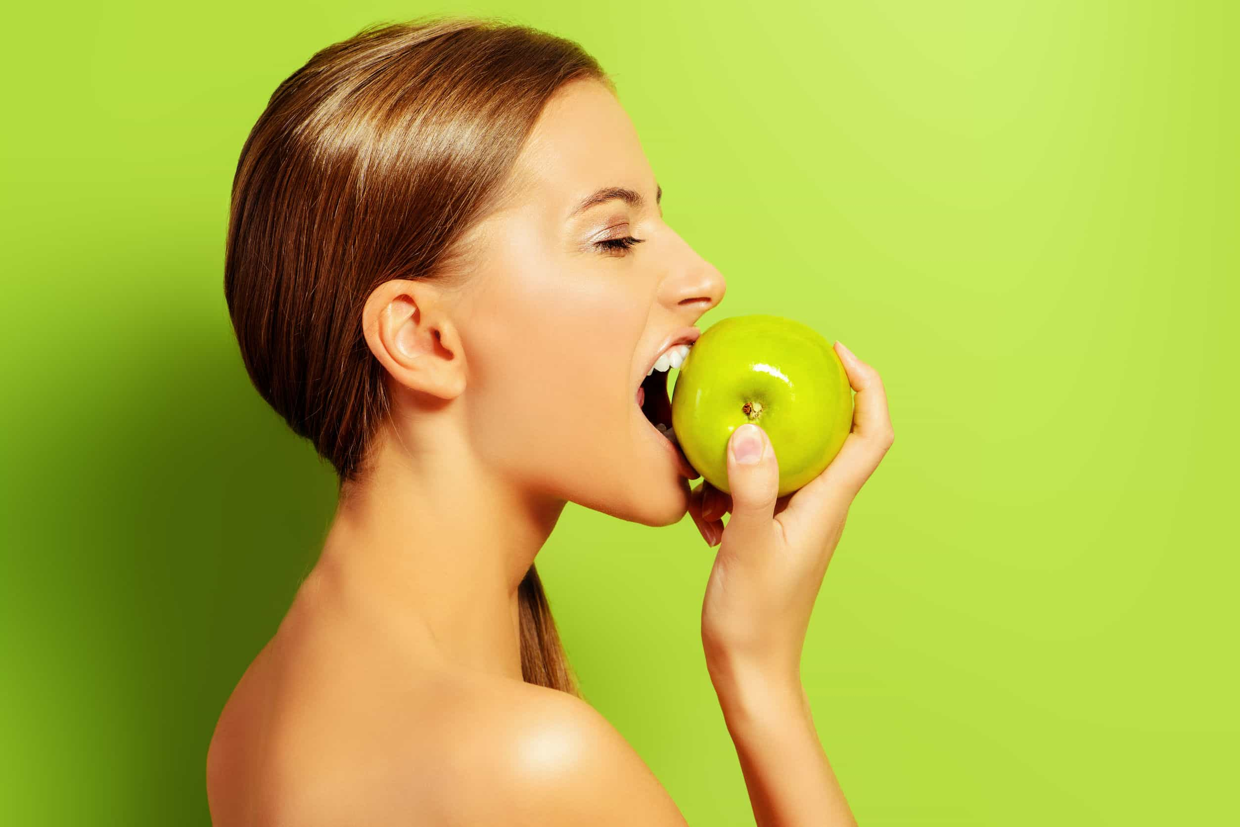 45031110 - pretty girl biting fresh apple over green background