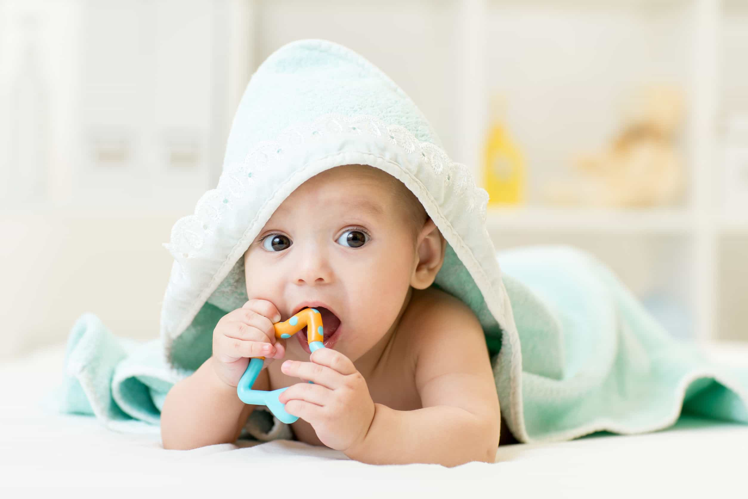 42593610 - baby with teether in mouth under bathing towel at nursery