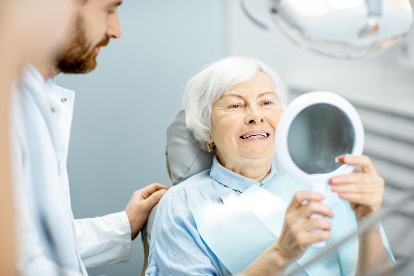Elderly woman enjoying her smile in the dental office